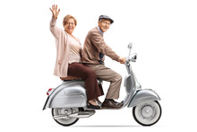 Senior Couple Riding A Vintage Scooter And Waving