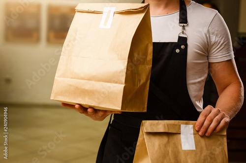 Fototapeta Two boxes with fast food being carried by delivery man in uniform for one of clients obraz