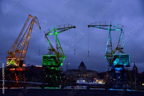 Obraz Barwnie oświetlone zabytkowe żurawie na nabrzeżu Szczecina Łasztownia - fototapety do salonu