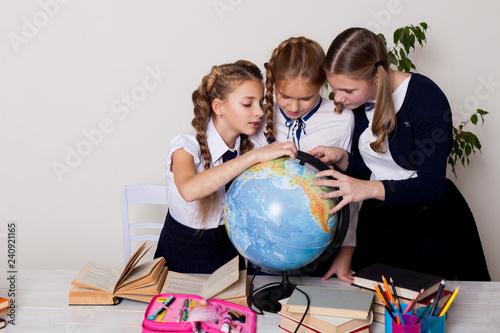 Αφίσα  three girls in the school geography lesson learn globe knowledge