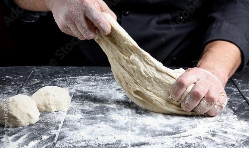 Recess Fitting Bread chef in black uniform kneads white wheat flour dough