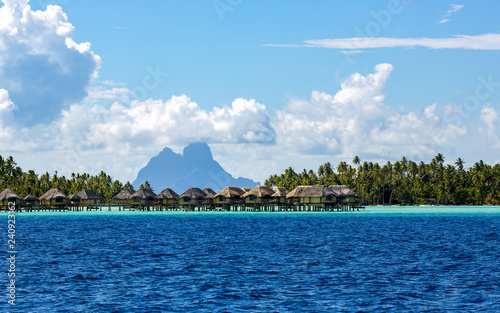 Fototapeta Luxury overwater thatched roof bungalow resort on a wooden pontoon in the clear blue lagoon on Bora Bora in French Polynesia