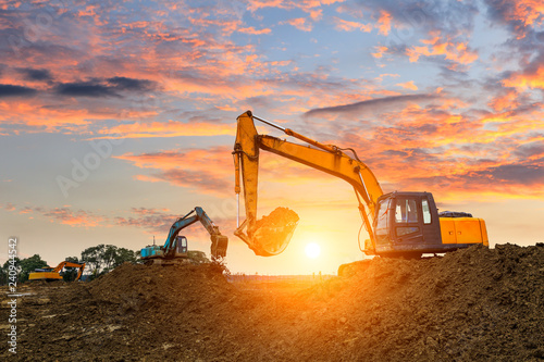 Obraz Three excavators work on construction site at sunset - fototapety do salonu