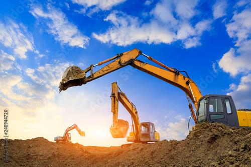 Fotografía  Three excavators work on construction site at sunset