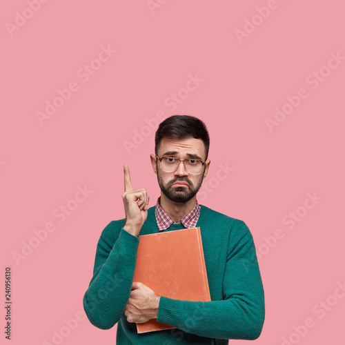 Fotografie, Obraz  Unhappy displeased guy frowns face, indicates with index finger above, wears spe