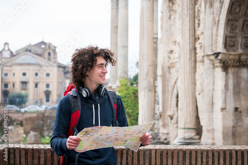 Foto  Handsome tourist holding a tourist map near Roman forum in Rome, Italy