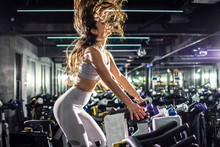 Side View Of Slim Sporty Young Woman Riding Exercise Bike On Cycling Training At Gym