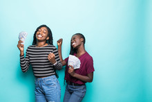 Two Pretty African Young Girls Friends Standing Showing Money Banknotes, Celebrating Isolated Over Green Background