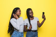 Leinwandbild Motiv Young beauty african woman make video call or selfie on phone isolated on yellow background