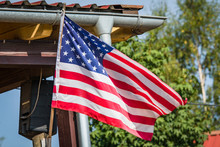American Flag On A Porch Outside A Small Cabin