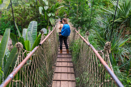 Fotografía  Woman with a backpack taking photographs on a suspension bridge in the jungle