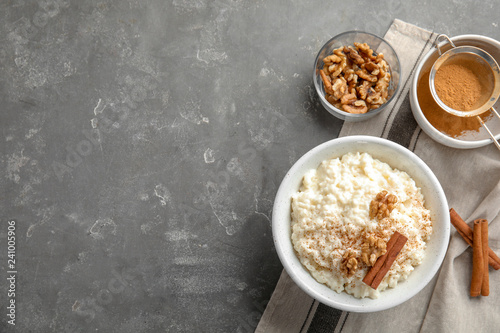 Creamy rice pudding with cinnamon and walnuts in bowl served on grey table, top view. Space for text