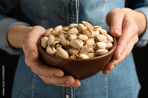 Woman holding bowl with pistachio nuts on black background, closeup