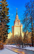 Vibrant sunny view of winter campus of famous Russian university with snowed evergreen trees