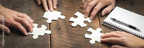 Fotografia  Hands Of Business Team Piecing Together Puzzle On Wooden Conference Table With P