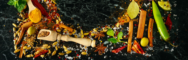 Variety of spices and herbs on kitchen table. Flat lay, top view. Wide photo.