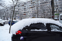 View Of The Black Car In The Snow In The City In Winter.