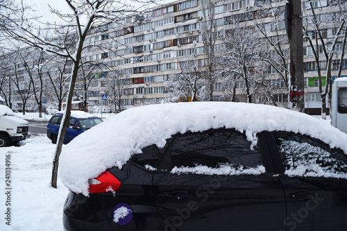View of the black car in the snow in the city in winter. фототапет