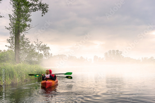 Two girls kayaking in a beautiful morning landscape