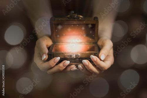 Photo opened wooden magic box on hands, lights from little chest, dreams in hands, bel