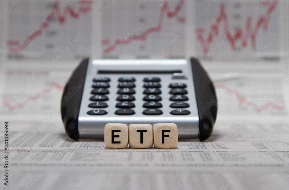 Fototapeta ETF word built with cube infront of a calculator