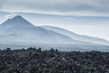 volcanic landscape with black lava field and volcano