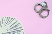 Police Handcuffs And Hundreds Of Us Dollars Lie On A Pink Background