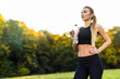 Thirsty fitness female jogger drinking fresh water after training. Young athletic woman exercising in the park outdoors.