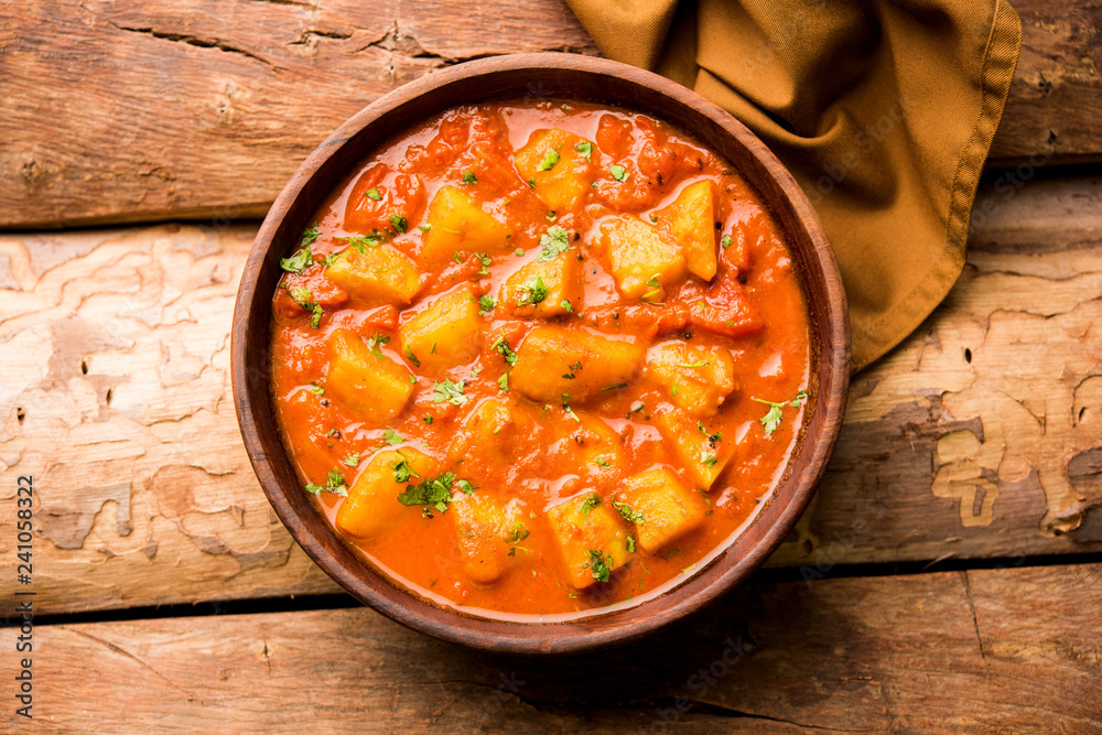 Fototapety, obrazy: Indian food - Aloo curry masala. Potato cooked with spices and herbs in a tomato curry. served in a bowl over moody background. selective focus