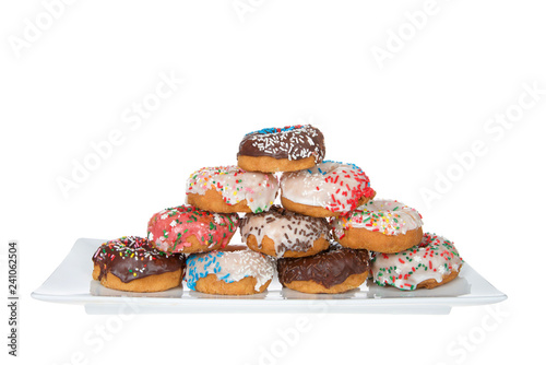 Rectangular plate with frosted cake donuts stacked, covered with candy sprinkles in various colors, Isolated on white.