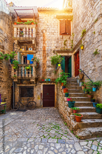 Wall Murals Narrow alley Narrow street in historic town Trogir, Croatia. Travel destination. Narrow old street in Trogir city, Croatia. The alleys of the old town of Trogir are very picturesque and full of charm. Croatia.