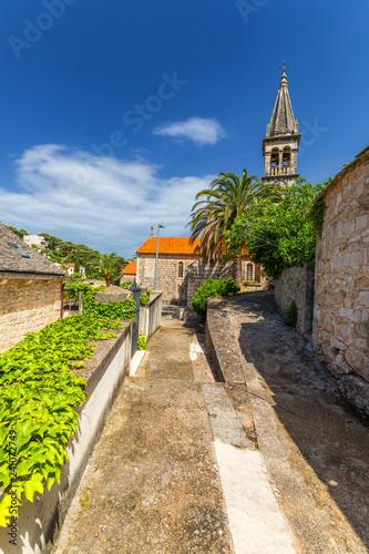Spoed Foto op Canvas Zuid-Amerika land Church building and palm tree against sunny blue sky in Splitska village on Brac island, Croatia.