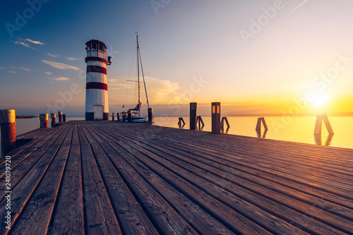 Foto auf Leinwand Leuchtturm Lighthouse at Lake Neusiedl, Podersdorf am See, Burgenland, Austria. Lighthouse at sunset in Austria. Wooden pier with lighthouse in Podersdorf on lake Neusiedl in Austria.