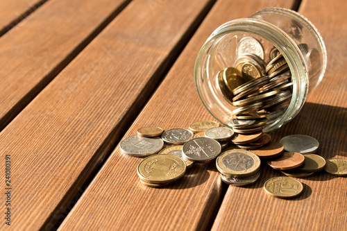Foto Various coins are scattered on a wooden table