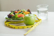 Good food for good health. Breakfast meal apple and water on the table and measure tape.