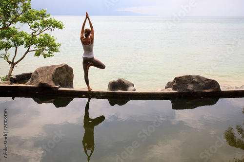 In de dag Ontspanning Woman practicing morning meditation Yoga at the beach