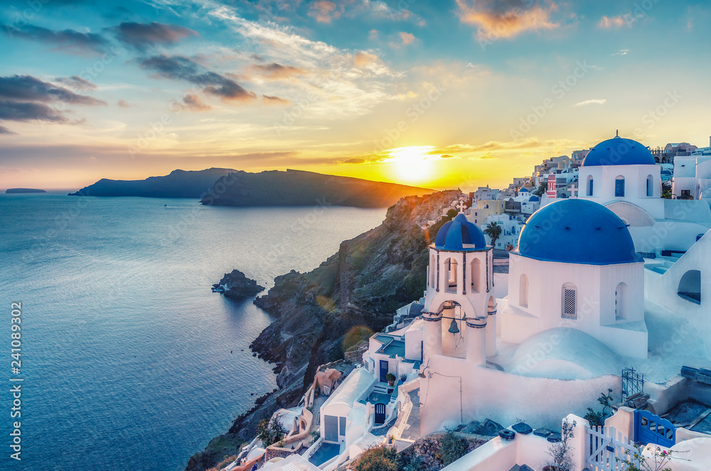 Fototapeta Beautiful view of Churches in Oia village, Santorini island in Greece at sunset, with dramatic sky.