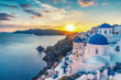 Leinwandbild Motiv Beautiful view of Churches in Oia village, Santorini island in Greece at sunset, with dramatic sky.