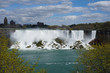 Niagara Falls waterfall on bright spring day with clouds and blue sky as seen from Ontario, Canada
