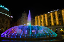 GENOA, ITALY, DECEMBER 11, 2018 - View Of The Colorful Fountain And Palace Of The Liguria Region Of De Ferrari Square By Night In Genoa, The Heart Of The City, Italy.