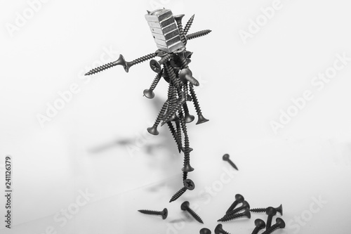 Photo sur Toile Art Studio Abstract figurine of black self-tapping screws hanging on the magnet