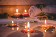 relaxing spa background with candles floating in the bath water, some green petals and a towel near the water surface