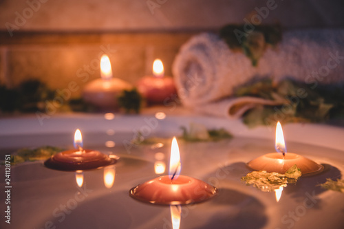Fototapeta relaxing spa background with candles floating in the bath water, some green petals and a towel near the water surface obraz