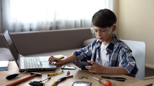 Curious Boy In Safety Glasses Searching For HDD Instructions On Laptop, Hobby