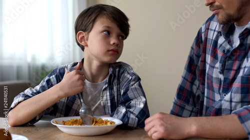 Little sad boy mixing cornflakes with spoon, looking at father, poor appetite Wallpaper Mural