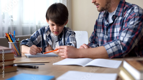 Dad sitting at the table and making his capricious son to do homework, education Tablou Canvas