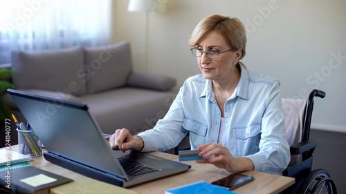 Valokuva  Handicapped senior lady entering card number on laptop, purchase in online shop