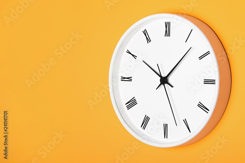 White round clock with black numbers isolated on orange wall. Time perspective empty copy space background.