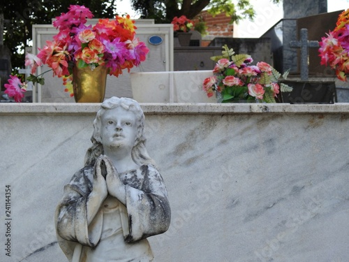 Fotografering  Scene in a cemetery: stone statue of a girl with hands together, praying, looking up
