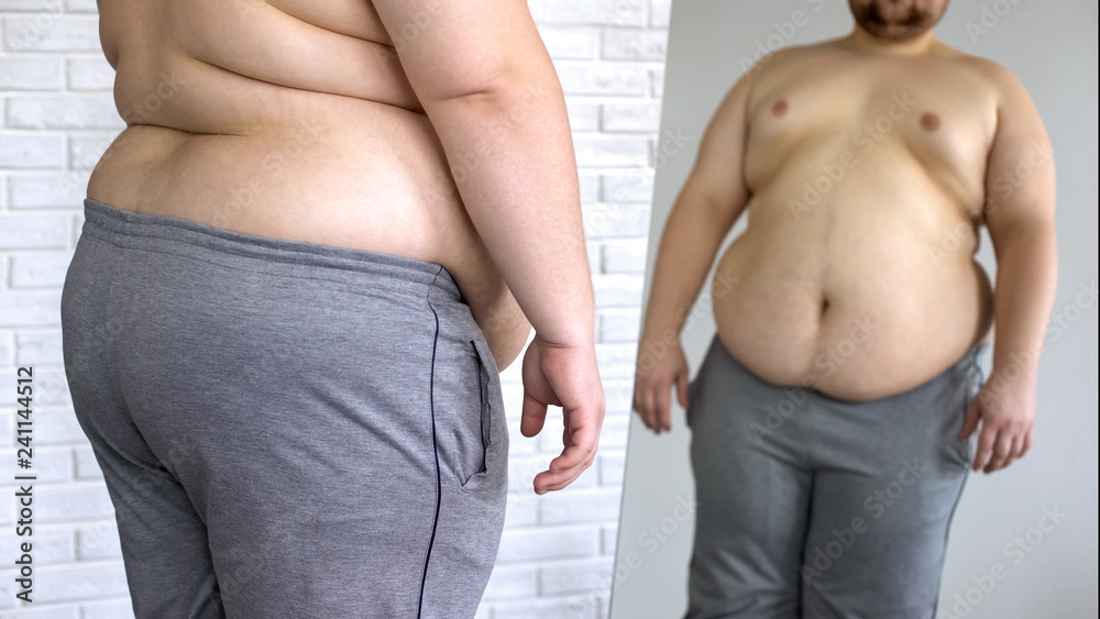 Fototapeta Sad overweight man looking at fat belly mirror reflection, weight loss problem